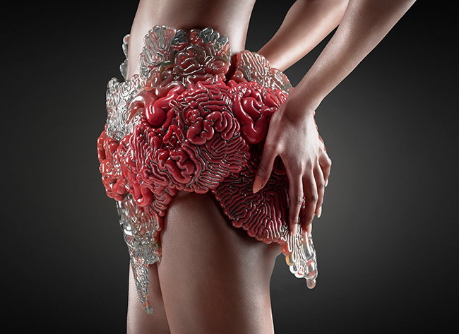 Mushtari, a 3D printed wearable that can change color, create food, and produce biological tissues, such as insulation for the body, designed to enable human survival on distant planets and environments. Part of the Wanderers series, the wearable skin combines a continuous internal network of biocompatible fluidic channels with variable optical transparency through the use of bitmap-based multi-material additive manufacturing (2015). Project partners: The Mediated Matter Group, MIT Media Lab; Stratasys, Ltd. Photo: Yoram Reshef. Courtesy of Neri Oxman and The Mediated Matter Group