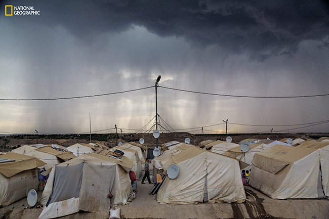 TURKEY 2014 Stranded but sheltered Rain clouds cast a shadow over Nizip 1, a camp where more than 30,000 Syrian refugees make do in tents provided by a Turkish governmental aid agency. Each unit has a small kitchen, bedding, and a TV. People share toilets and showers. (Photograph by John Stanmeyer / National Geographic)