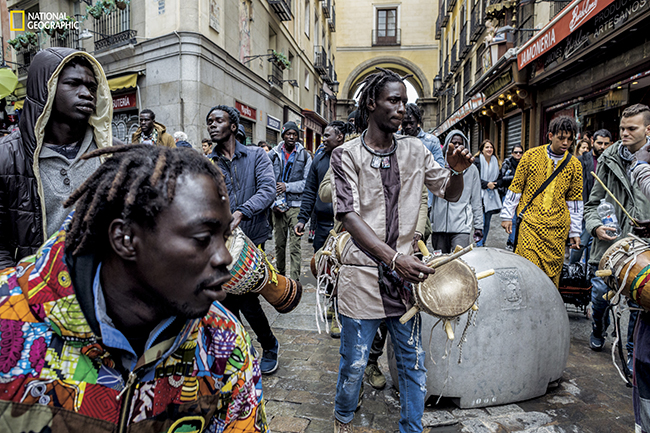 At an entrance to Madrid's historic Plaza Mayor, Senegalese migrants take a break from their labors for an autumn celebration of drumming, singing, and prayerful thanks. In urban Spain, many Africans have been unable to obtain formal work permits. A popular alternative: peddling merchandise on blankets that can be whisked away when police show up. The salesmen are called manteros, blanket men. (Photograph by Aitor Lara / National Geographic)